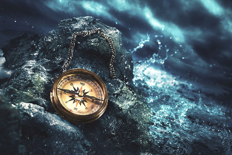 The Pirate's Code. An image of a compass on a boulder, with a stormy, evening sea in the background.